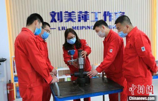 """刘美萍正给技巧 员们解说 改进  后的""""第二代防漏油装置""""。 李雅林 摄"""