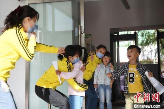 图为幼儿复课,与老师拥抱。 杨艳敏 摄