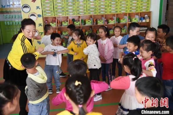 """图为教师史春梅教授幼儿用""""胳膊肘轻挨对方胳膊肘""""的方式表示友好,用寓教于乐的方式将防疫知识贯穿其中。 杨艳敏 摄"""