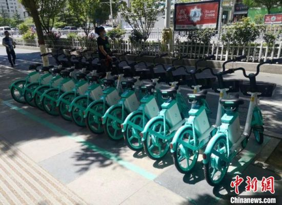图为兰州街头的共享单车,摆放整齐,按颜色划分了停车区域。(资料图) 张鑫 摄