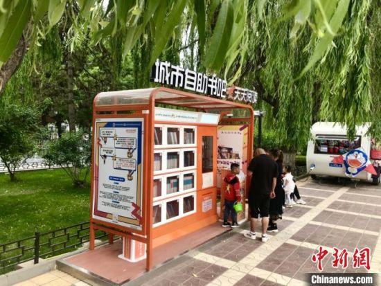 """6月4日,一家三口在黄河风情线沿线的""""城市自助书吧""""扫码借阅图书。 闫姣 摄"""