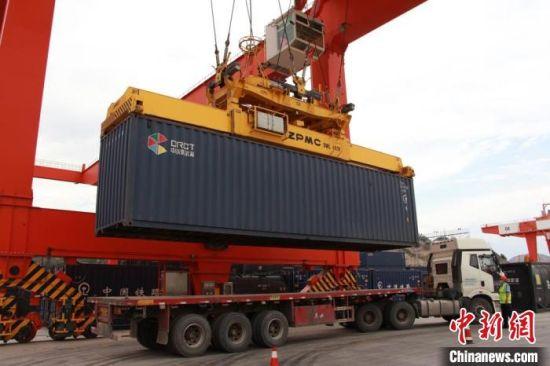 图为正在装上货运班列的集装箱。 李同 摄