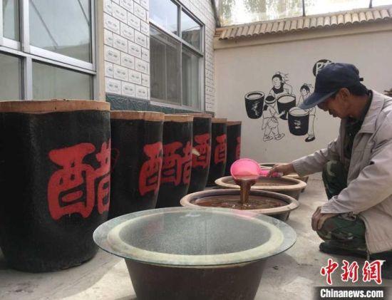 图为红旗村村民郭泰山在自家院子支摊开起手工醋坊。 张婧 摄