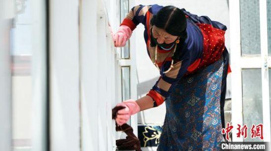 图为尕秀村村民擦自家阳台窗户。 魏建军 摄