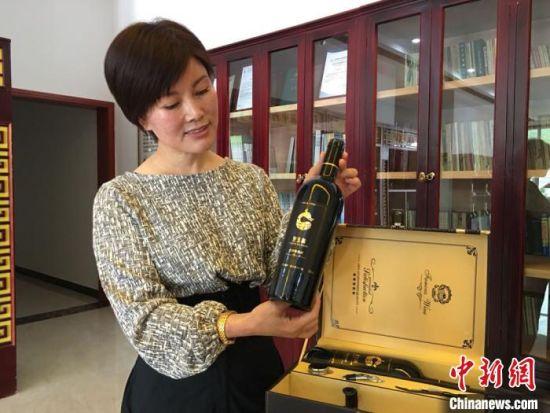 图为王玉兰向记者展示企业研发的党参葡萄酒。 张婧 摄