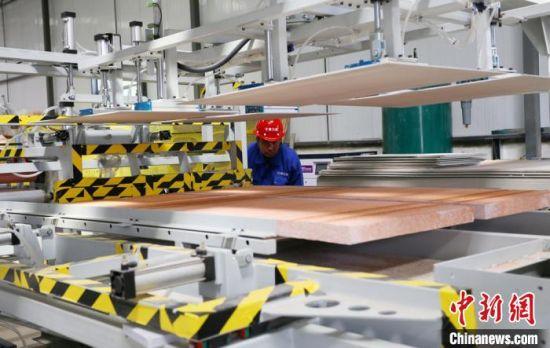 兰州高新区的甘肃元能新型材料科技有限公司生产车间,工人正在控制机床生产复合墙板。(资料图) 高展 摄