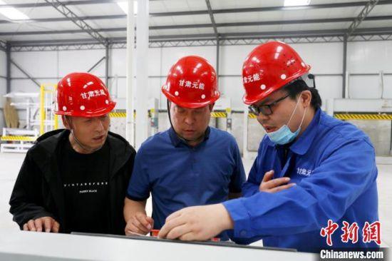 甘肃元能负责人任林(中)正与员工一起调控数字机床。(资料图) 高展 摄
