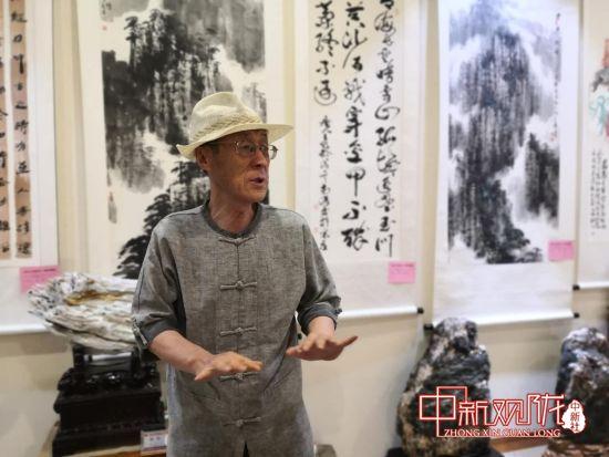 甘肃飞天书画学会会长抗文生介绍画展情况。