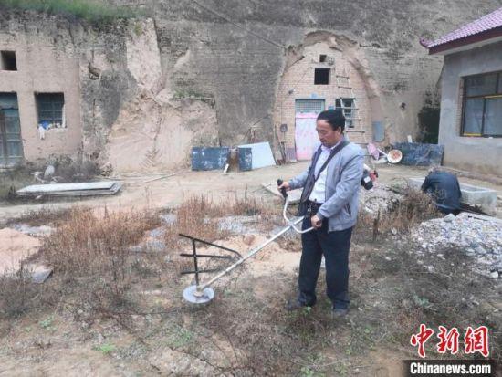 图为胡建国帮助贫困户清理院落杂草。(资料图) 杨康 摄