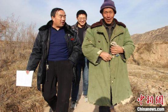 图为胡建国到田间地头了解贫困户家庭产业情况。(资料图) 杨康 摄