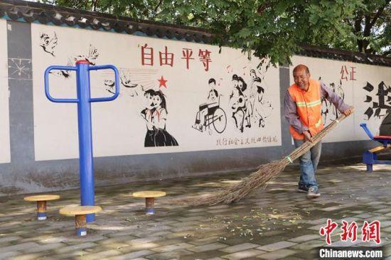 甘肃庆阳市西峰区后官寨镇沟畎村公益性岗位保洁员清扫文化广场。(资料图) 盘小美 摄