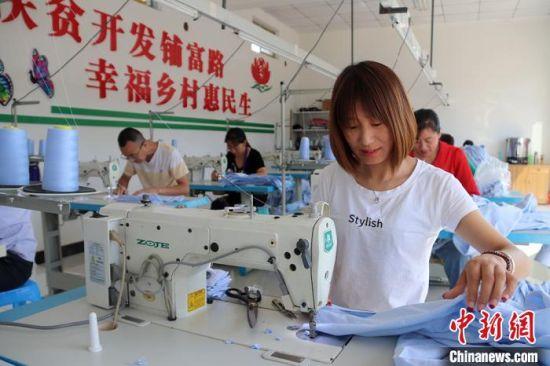 什社乡李岭村扶贫车间工人在制作服装。(资料图) 盘小美 摄