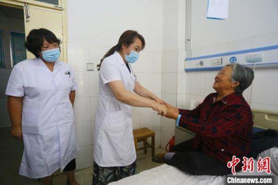 7月下旬,甘肃省平凉市静宁县人民医院内,对口帮扶的天津市武清区人民医院专家(左一)陪同该院医生一同查房。 高展 摄