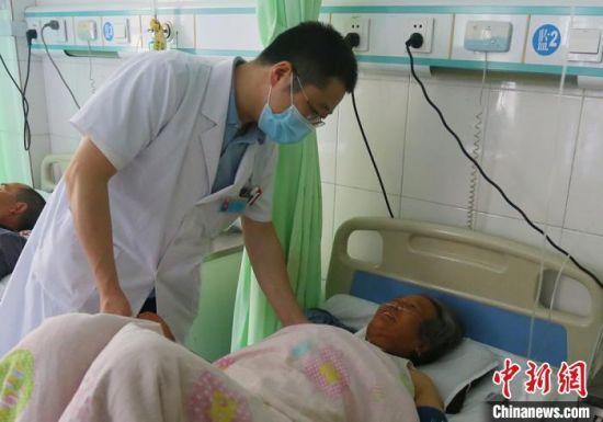 图为静宁县人民医院胸痛中心心内科主任韩飞查看患者情况。 高展 摄