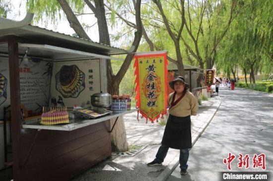 """关城脚下的杏皮水、桂花糕、凉皮等地方小吃更是让游客多了一份与当地的亲近感,当地商贩穿上古代服饰,彷佛让游客""""穿越""""至古丝路畅游。 谢生亮 摄"""