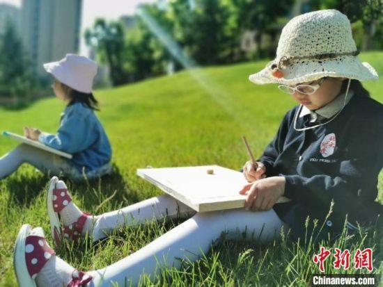 图为北大附属实验学校幼儿园孩子们在校园草坪上开展活动。北大附属实验学校幼儿园提供