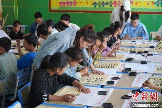 图为实践团成员教孩子们写毛笔字。 王玉丰 摄