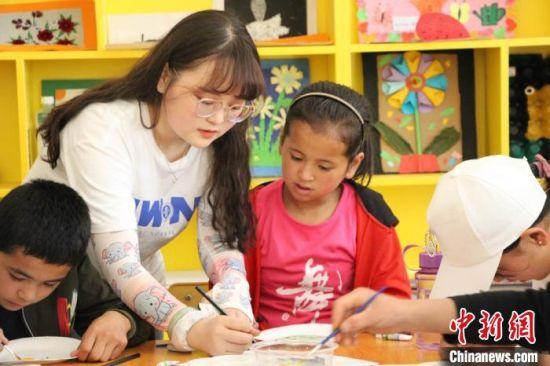 图为实践团成员教孩子们画画。 王玉丰 摄