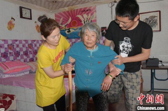 朱红红与儿子一起照顾婆婆罗水花。(资料图) 白勇涛 摄