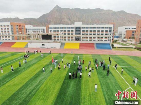 历经去冬今春10个月时间,临夏国强职业技术学校建成。图为当地学生参观学校。(资料图) 甘肃二建集团十六公司供图