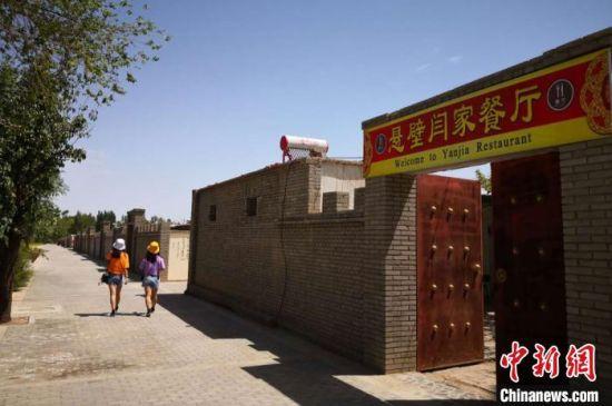 """长城脚下的旅游村深挖""""长城文化"""",农家乐的外墙设计为老旧的古城墙一般,让游人彷佛有穿越之感的神秘。 丁思 摄"""