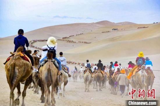 8月11日,游客骑骆驼畅游鸣沙山,观赏大漠如画美景。 王斌银 摄