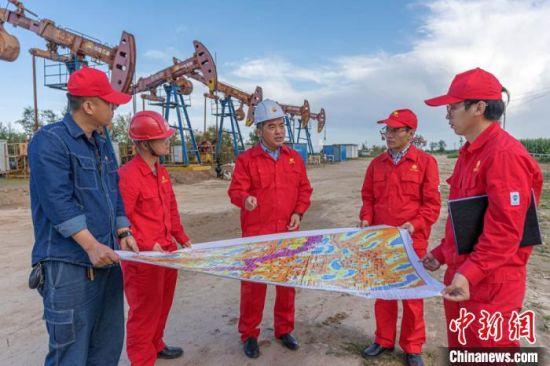 图为脉冲采油技术团队在西峰油田采油井场探讨轮采轮注不同区域开发规律。 李忠斌 摄