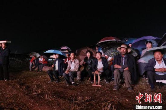 图为普法艺术作品演出现场,村民冒雨看节目。(资料图) 定西市司法局供图