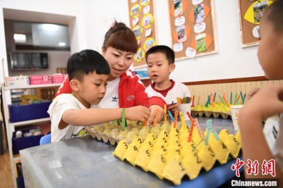 图为老师利用废弃的鸡蛋托盘,引导孩子们在游戏中创意学习,培养良好的行为习惯。 杨艳敏 摄