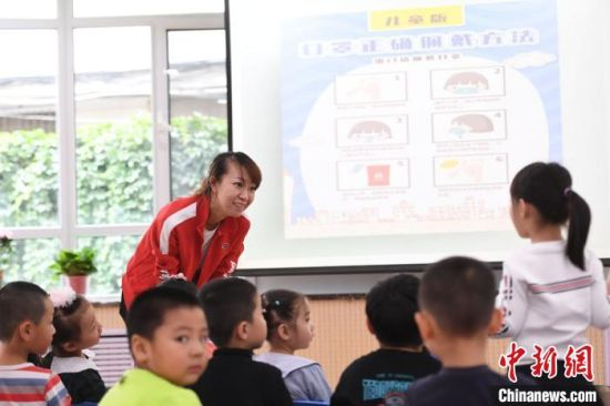 """图为老师通过""""知识问答""""的形式,为孩子们讲解健康的卫生生活习惯。 杨艳敏 摄"""