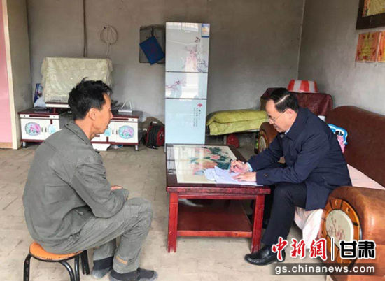 庆阳市委统战部常务副部长罗君伟在帮扶户家中完善扶贫资料。