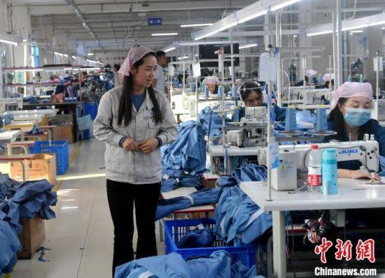 甘肃榕发服装智造公司的工作车间 ,该车间缝一组组长张桃玉正在工作中。 吕明 摄