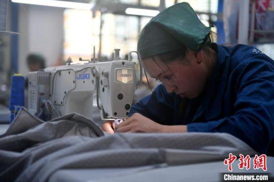 甘肃榕发服装智造公司的工作车间,陈娟娟正在工作中。 吕明 摄