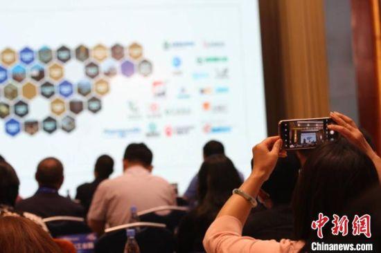 图为会议中的行业报告现场,参会人员用手机记录重要片断。 殷春永 摄