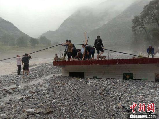 图为灾后村民从饮水点抽水至村里。(资料图)受访者提供