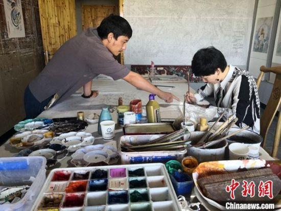 """图为2020年8月下旬,敦煌""""80后""""画家张杰龙(左)在为云南丽江""""学生""""莫北讲解敦煌壁画的绘画技巧。 冯志军 摄"""