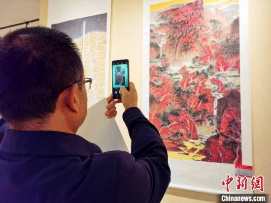 """10月12日,""""'脱贫攻坚 读者同心'中国书法之乡・镇原书画作品巡展""""在兰州开幕。图为书画爱好者拍摄展览作品。 高展 摄"""