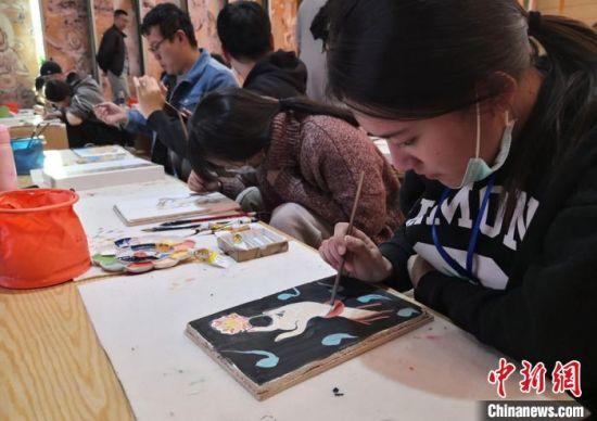 """台湾大学生在敦煌""""莫高学堂""""体验泥胚画手作课程,学习壁画临摹,试图通过自己的理解呈现心中的""""莫高窟""""。 丁思 摄"""