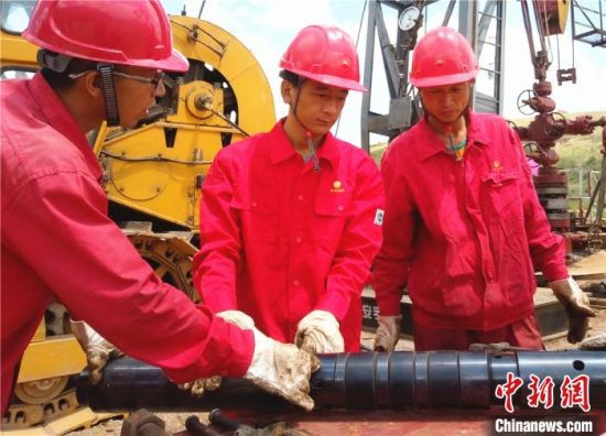 杨义兴(中)与团队成员共同研究改进新型打捞工具。(资料图)受访者供图
