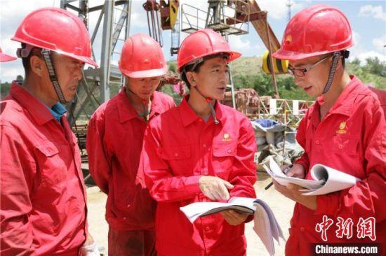 杨义兴(右二)和工友探讨修井方案。(资料图)受访者供图