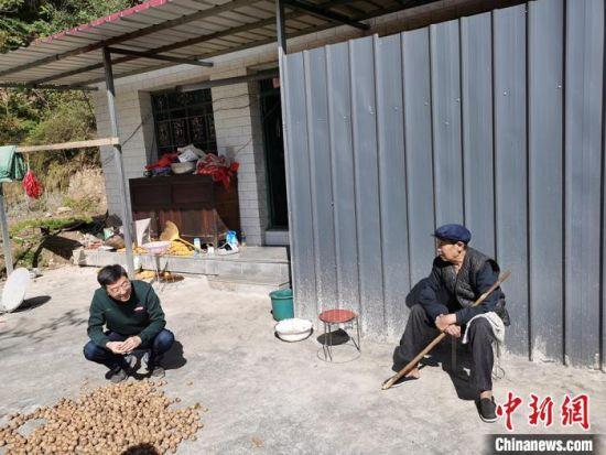 """10月下旬,邱琦(左)在崔马村村民马吴怀家里""""唠嗑""""。 吴鹏 摄"""
