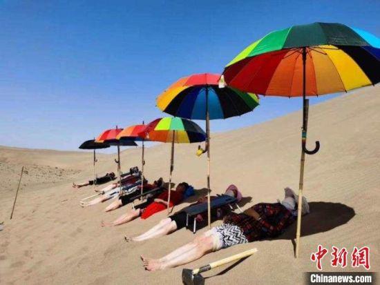 每年仲夏时节,在甘肃酒泉金塔县金嘉路7公里处的沙漠边缘,一大批游客或躺、或埋、或睡,将身体藏进滚烫的沙子里,体验沙疗带来的神奇疗效。(资料图) 卢玉 摄