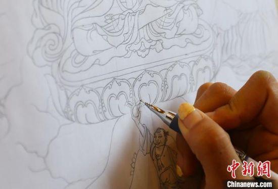 卓玛才让在用笔勾勒唐卡线稿。 高展 摄