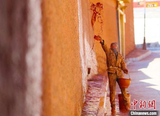 """11月上旬,夏河县拉卜楞寺内,匠人用传统泼洒方法为寺院墙壁""""美颜""""。 高展 摄"""