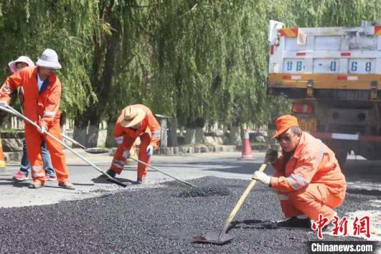 养护工修补油路。(资料图)受访者供图
