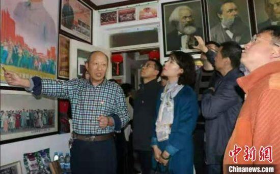 现居住于甘肃省嘉峪关市的古稀老人张天顺在不到60平方米的家里,布置起了爱国主义教育基地。图为张天顺(左一)向参观者进行讲解。(资料图)受访人供图