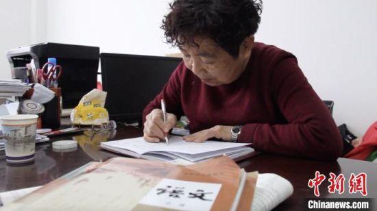 图为58岁的闫桂珍伏案做笔记。今年,是她从东北来到嘉峪关市的第35年。 高莹 摄
