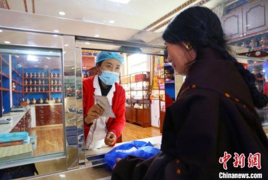 图为藏族民众正在窗口抓取藏药。 高展 摄