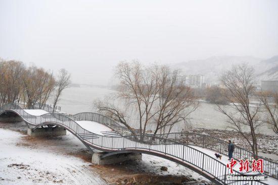 12月2日,甘肃兰州迎来降雪,市民在黄河步道上散步赏雪景。中新社记者 杨艳敏 摄