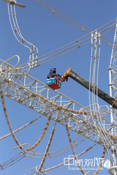 ±800千伏祁连换流站年检现场,电力员工正在开展高空设备检查。尹岚 摄